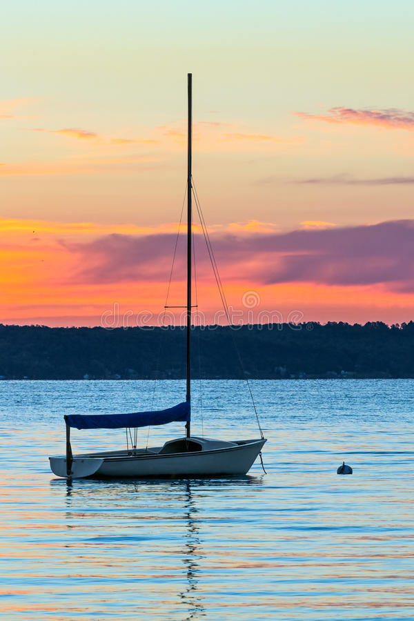 Daybreak on Crystal Lake. The sunrise sky silhouettes the tall mast of a small sailboat on Michigan's Crystal Lake royalty free stock images