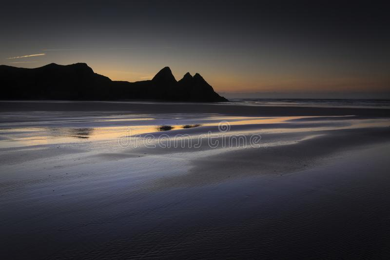 Daybreak op Three Cliffs Bay stock foto's