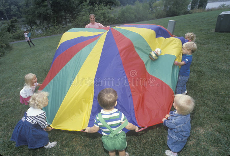 Daycare children playing a parachute game stock photos