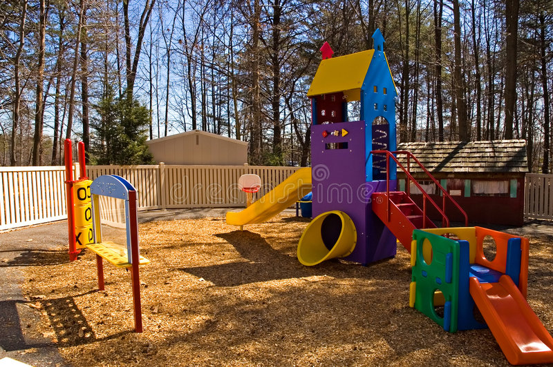 Daycare playground equipment. Colorful children's playground equipment at a daycare center with a variety of toys, including a slide and games to play on during stock photography