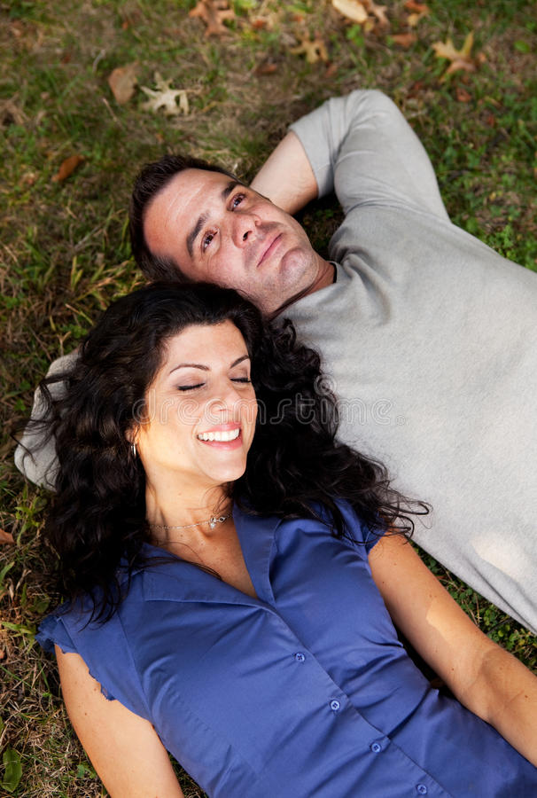 Daydream. A couple day dreaming while laying on grass stock photos