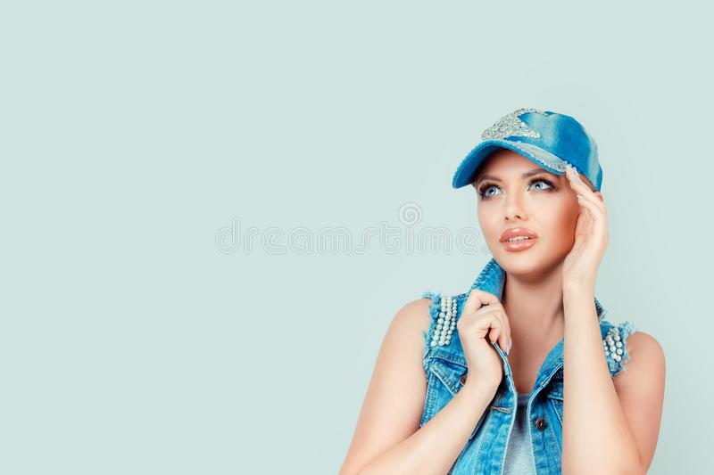 Daydream. Beautiful woman looking up at copy space above hand, thinking, daydreaming hand on cheek, isolated grey wall background royalty free stock photography