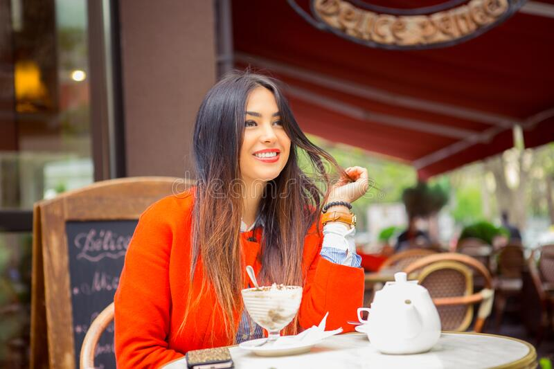 Daydream in coffee shop. Portrait young Indian asian businesswoman smiling touching hair looking away waiting for boyfriend friend. To come royalty free stock photos