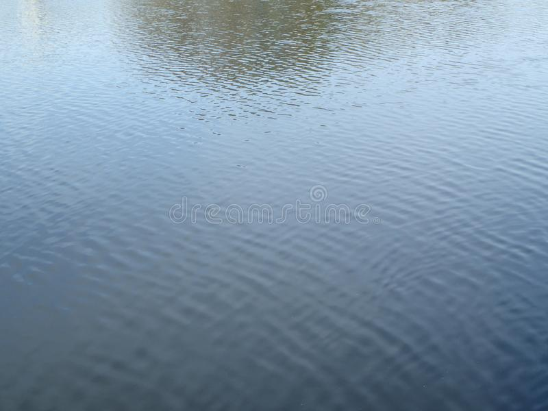 Daydream water. Surface of water. Small wrinkles in grey and blue. You expect birds to swim in. absolute silence and solitude . Meditating over water. Cool wet royalty free stock images