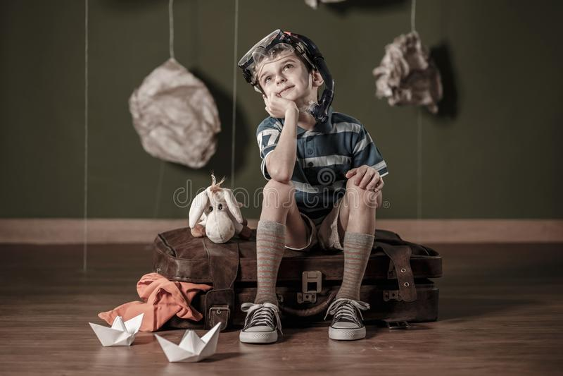 Daydreamer pequeno que senta-se na mala de viagem fotos de stock royalty free