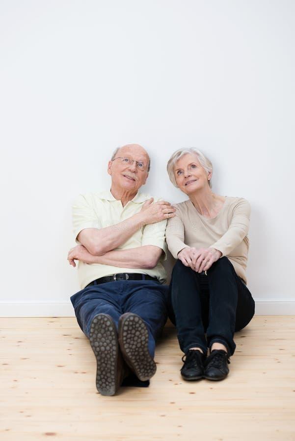 Daydreaming пожилых пар сидя в новом доме стоковая фотография