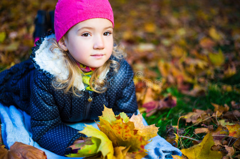 Daydreaming beautiful little girl with maple leaves lying in aut royalty free stock image