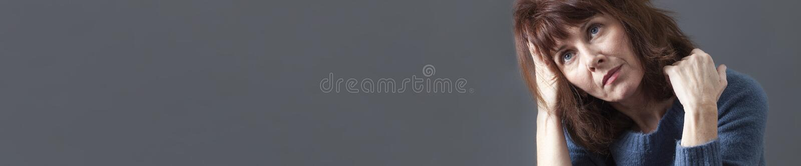 Daydreaming beautiful 50s woman looking contemplative, gray copy space banner royalty free stock photo