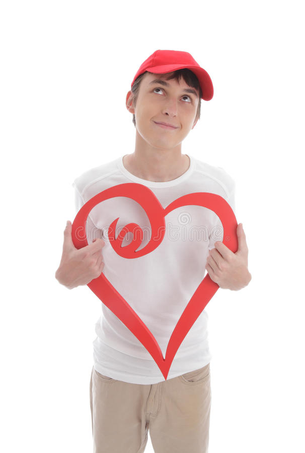 Daydreaming boy holding red love heart. Daydreaming teenage boy holding a red valentine love heart. Space for copy or message stock images