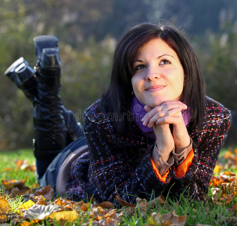 Daydreaming girl in autumn. Beautiful young woman daydreaming on the ground in autumn stock photos