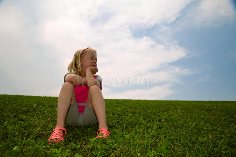 Daydreaming Little Girl. Little girl staring off into the distance daydreaming royalty free stock image
