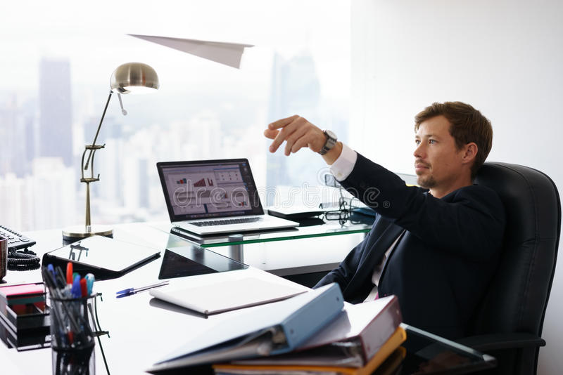 Daydreaming Successful Man Office Worker Throwing Paper Airplane. Corporate manager in modern office takes a break and prepares a paper airplane. The bored man royalty free stock photo