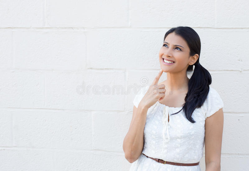 Daydreaming woman. Closeup portrait, charming upbeat smiling joyful happy young woman looking upwards daydreaming something nice, isolated outdoors white royalty free stock photo