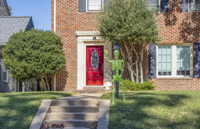 Dayglo Halloween skeleton attached to lamp post outside upscale brick house with beautiful bright red front door royalty free stock photo