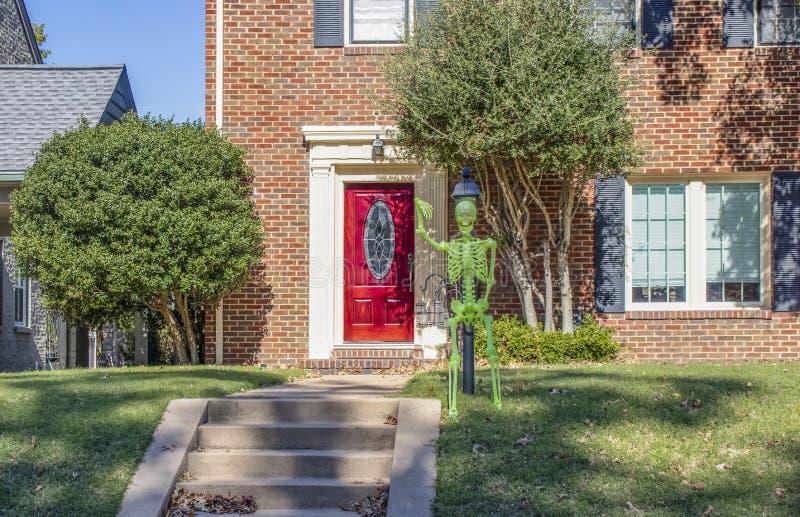 Dayglo Halloweenowy kościec dołączał latarnia na zewnątrz ekskluzywnego cegła domu z pięknym jaskrawym czerwonym dzwi wejściowy zdjęcie royalty free