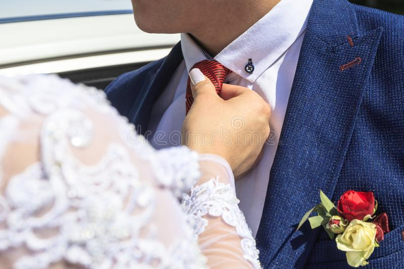 Daylight. Bride straightens the groom& x27;s red tie. have toning. Flower, background, family, woman, business, wedding, fashion, floral, hand, retro, love stock photography