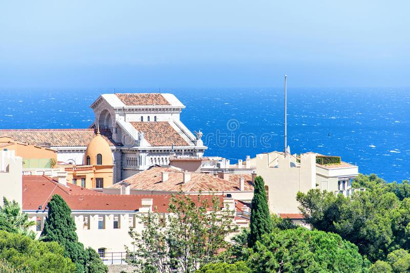 Daylight closeup view to old town Chateau Grimaldi palace. Trees, bright blue sky and sea on background. Negative copy space, place for text. Monte Carlo royalty free stock photos