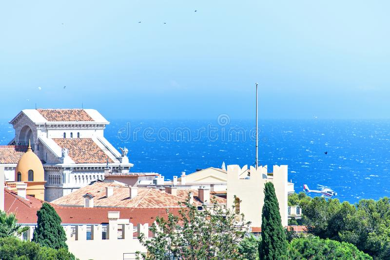 Daylight closeup view to old town Chateau Grimaldi palace. Trees, bright blue sky and sea on background. Negative copy space, place for text. Monte Carlo royalty free stock image
