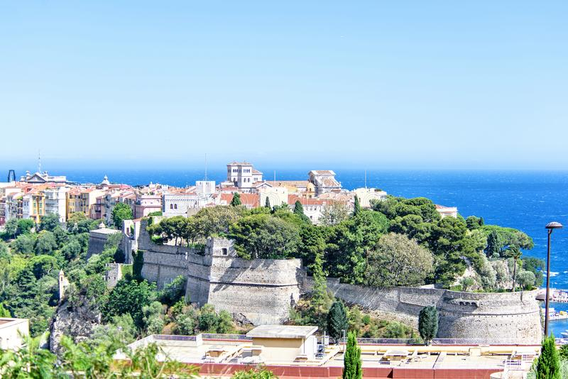 Daylight closeup view to old town Chateau Grimaldi palace. Trees, bright blue sky and sea on background. Negative copy space, place for text. Monte Carlo royalty free stock images