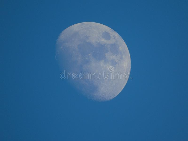 Daylight moon shines bright in evening blue sky over St Andrews royalty free stock photography
