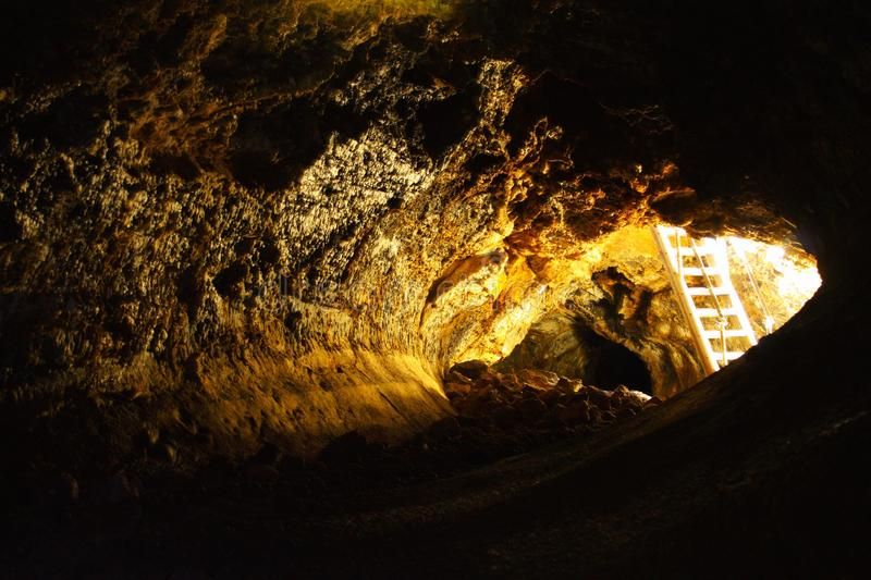 Daylight reflected in Golden Dome Cave in Lava Beds National Monument, California, USA. Ladder leading into Golden Dome Cave, one of the larger lava tube caves royalty free stock image
