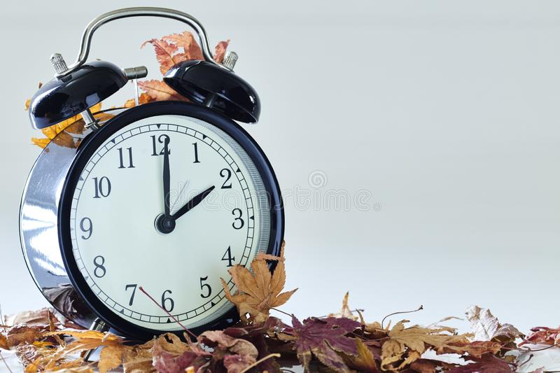 Daylight Saving Time End. Image of autumn Time Change, Fall back concept, Dry leaves and vintage alarm Black Clock on wooden table outdoors at afternoon,for text royalty free stock images