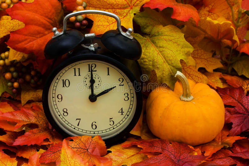 Daylight savings. Fall coloured leaves with a black clock, Fall Leaves stock image
