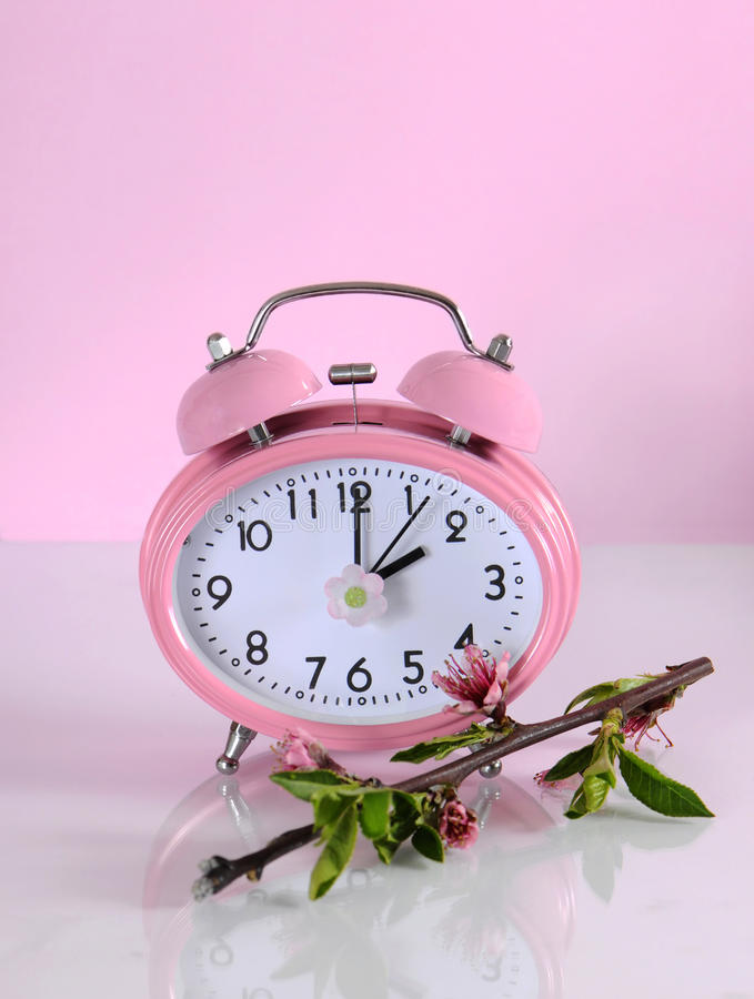 Daylight savings time begins clock concept for start at Spring. Against a pink background stock photos