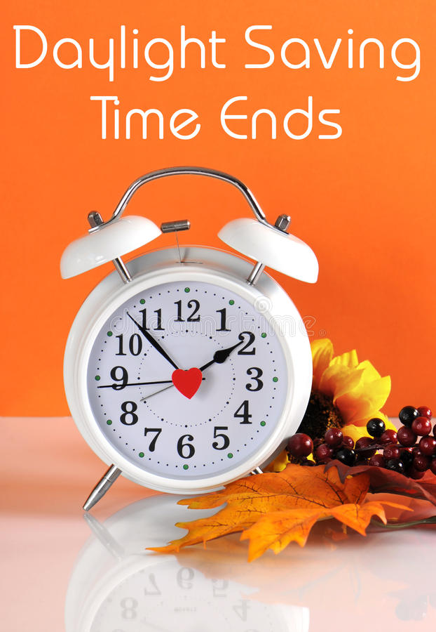 Daylight savings time ends in autumn fall with clock concept and text message royalty free stock photo