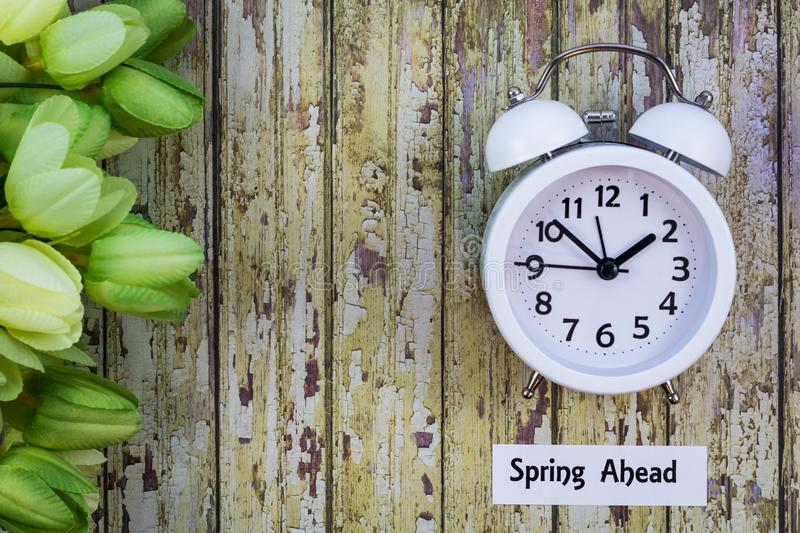 Daylight Savings Time Spring Ahead concept top down view with white clock and green tulips stock images