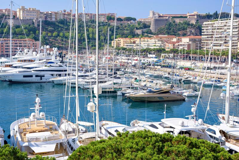 Daylight sunny view to parked luxury yachts of Monaco city. MONACO, FRANCE - JUNE 28, 2017: Daylight sunny view to parked luxury yachts and tall buildings stock images