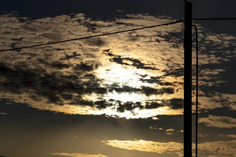 Daylight. sunset. autumn. the sun is reflected in the clouds. silhouette of a pillar with wires. electricity royalty free stock photos