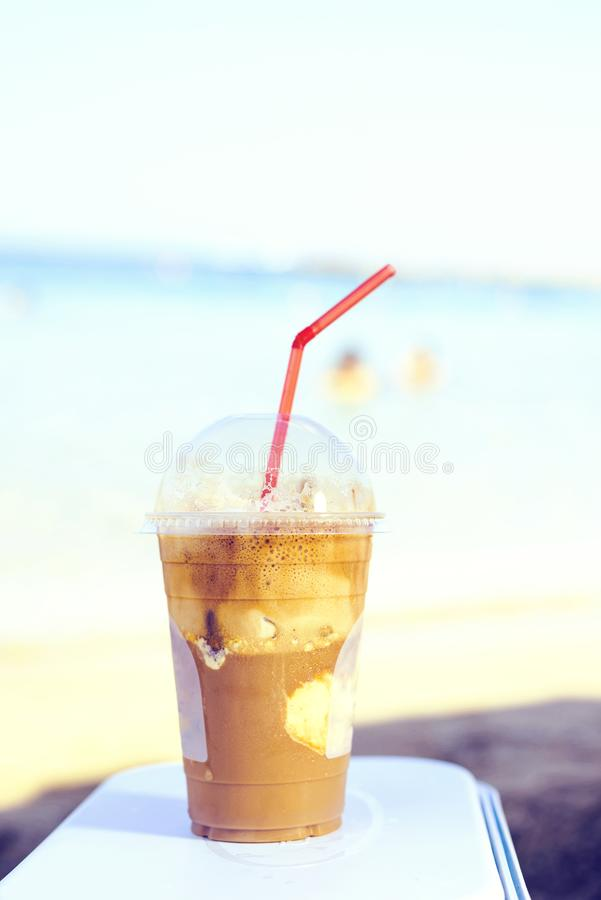 Daylight view to iced latte coffee drink near seashore royalty free stock image