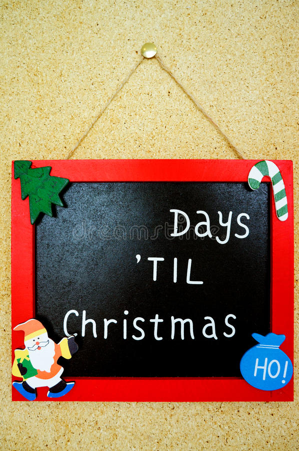 Days Until Christmas. A picture frame hanging on a wall with the words days til Christmas on it. The number of days remaining until Christmas is written on the stock images
