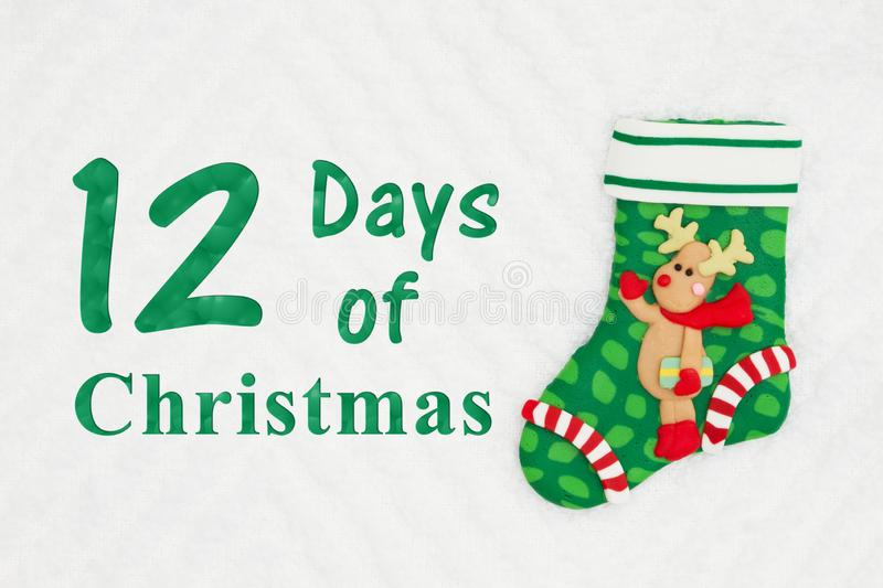 The 12 days of Christmas with a Christmas stocking with a reindeer. On white chevron textured fabric royalty free stock images