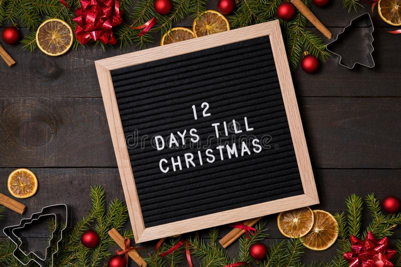 Twelve Days till Christmas countdown letter board on dark rustic wood. 12 Days till Christmas countdown felt letter board flatlay on dark rustic wood table with stock photography