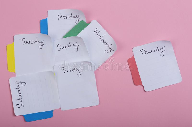 The days of the week - the paper stickers attached to the pink background stock photos