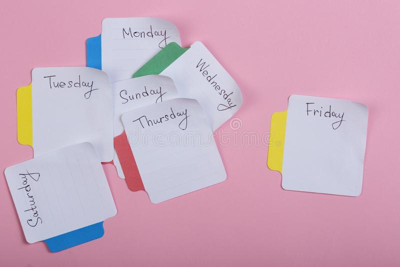 The days of the week - the paper stickers attached to the pink background stock photography