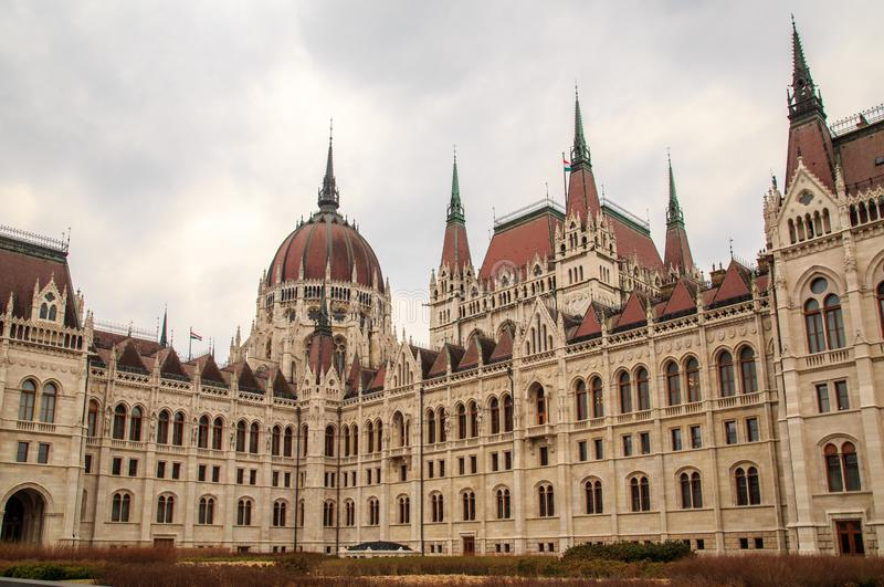 Daytime view of historical building of Hungarian Parliament, aka Orszaghaz, with typical symmetrical architecture and. Central dome on Danube River embankment royalty free stock image