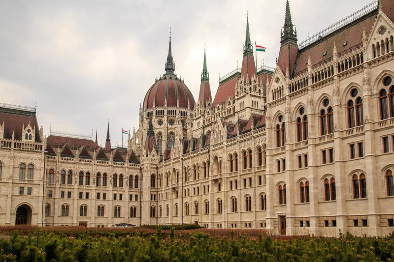 Daytime view of historical building of Hungarian Parliament, aka Orszaghaz, with typical symmetrical architecture and. Central dome on Danube River embankment stock photo