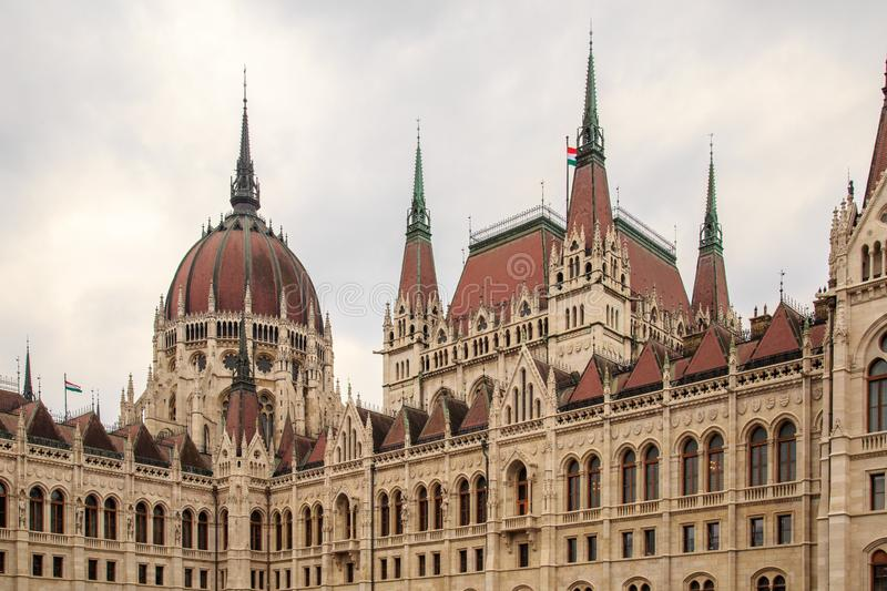 Daytime view of historical building of Hungarian Parliament, aka Orszaghaz, with typical symmetrical architecture and. Central dome on Danube River embankment stock image
