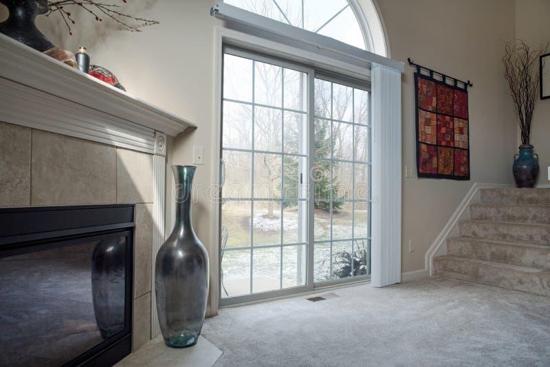 Winter View Through Patio Doors. Dayton, Ohio - November 28, 2018: Snowy winter scene as seen through living room glass patio doors royalty free stock photos