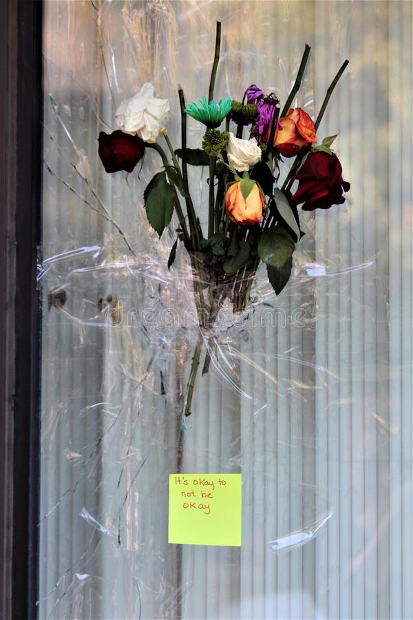 Dayton, Ohio / United States - August 7 2019: A bouquet covers a bullet hole. In an Oregon District window at the site of a shooting which killed nine and royalty free stock photos