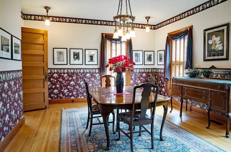 Victorian Dining Room Interior. Dayton, Ohio, USA - June 10, 2018: Example of Victorian dining room with flowered wallpaper in burgundy & cream satin stripe royalty free stock photo