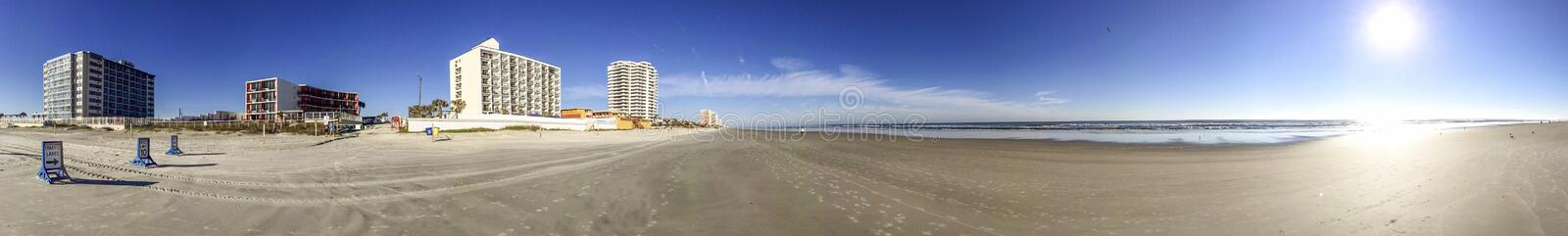 DAYTONA BEACH, FL - FEBRUARY 2016: Tourists walk along city beach. The city is a major attraction in Florida.  stock images