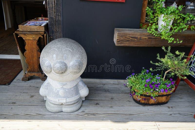 Dazaifu,日本- 2017年5月14日:Anpanman,普遍的芳香树脂字符,站立在商店前面的花岗岩石雕塑 免版税库存照片