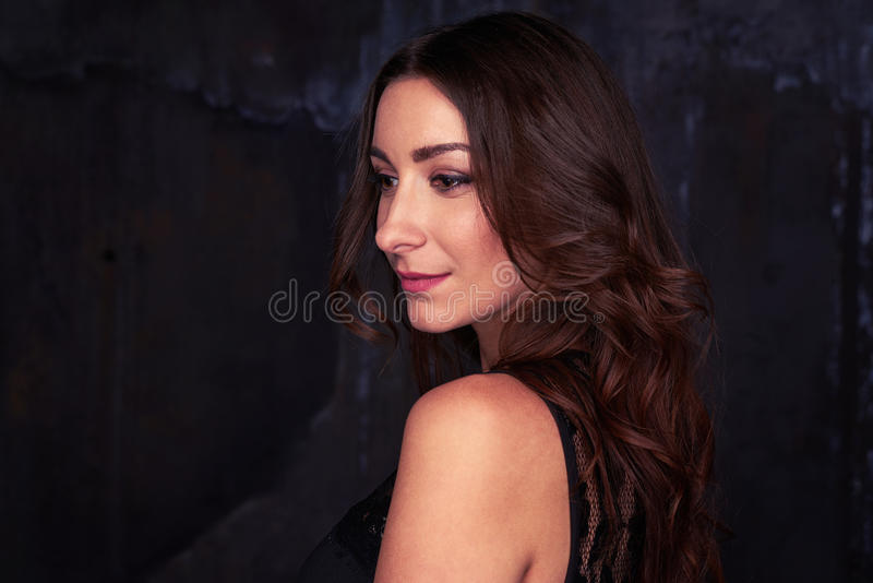 Dazzling female looking away from the camera with perfect make-up isolated over dark background royalty free stock image