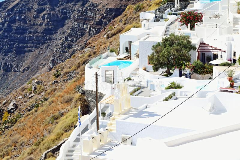 White clifftop village buildings Santorini Cyclades. Dazzling white buildings contrasting the black volcanic rocks of Fira village-traditional church and luxury stock photo
