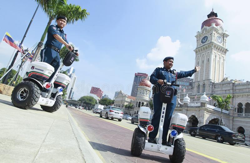 People. KUALA LUMPUR, MALAYSIA: DBKL Officers, on Segway while patrolling and controlling the route around Merdeka Square Central Zone on December 22, 2015 stock image