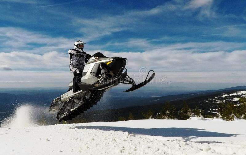 RIDER MAN WITH HELMET JUMPING WITH A SNOWMOBILE IN THE SUMMIT IN WINTER royalty free stock photos
